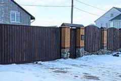 布朗篱芭和门由木头制成在街道在雪的路附近 免版税库存照片