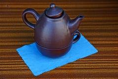 布朗茶壶和一个杯子在一块蓝色餐巾在一张棕色桌上 免版税库存图片