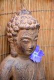 布朗菩萨雕象有竹芦苇背景和紫色花 免版税图库摄影
