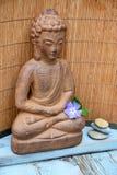布朗菩萨雕象有竹芦苇背景 免版税库存照片