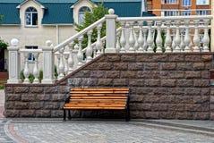 布朗长木凳在房子墙壁附近的围场 库存照片