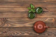 布朗陶瓷茶壶、两个深绿小特别杯子和新鲜薄荷在黑暗的木planked背景 茶道 库存照片