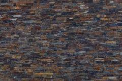 布朗,黑暗的板岩石墙背景 免版税图库摄影