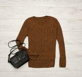 布朗黑毛线衣和黑袋子在木背景 秀丽蓝色聪慧的概念表面方式构成妇女 顶视图 免版税图库摄影