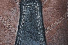 布朗绒面革缝合与与白色针的黑绒面革 免版税库存图片