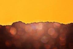 布朗bokeh光和橙色被撕毁的纸 图库摄影