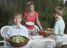 布置饭桌的母亲和儿子户外 免版税库存图片