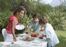 布置饭桌的母亲和儿子户外 免版税库存照片