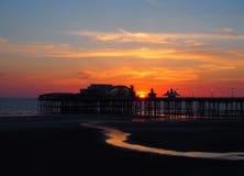 布莱克浦北部码头风景看法在发光的红色晚上光的在与有启发性桃红色和黄色天空和云彩的日落 免版税库存图片