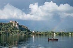 布莱德湖令人惊讶的照片在雨以后的在木小船的晚上与在天空的充满活力的彩虹和夫妇 库存图片