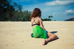 布裙的妇女坐热带海滩 免版税库存照片