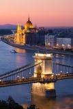 布达佩斯与铁锁式桥梁和议会大厦的都市风景日落 免版税库存照片