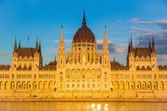 布达佩斯在与多瑙河,匈牙利,欧洲的日落期间被照亮的议会大厦 免版税图库摄影