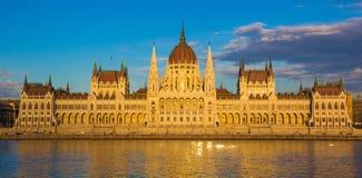 布达佩斯在与多瑙河,匈牙利,欧洲的日落期间被照亮的议会大厦 免版税库存照片