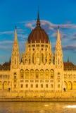 布达佩斯在与多瑙河,匈牙利,欧洲的日落期间被照亮的议会大厦 库存照片