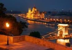 布达佩斯在晚上-横跨从Gellert小山和匈牙利议会的著名铁锁式桥梁看的多瑙河 库存照片
