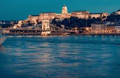 布达佩斯城堡和著名铁锁式桥梁在布达佩斯在晚上 免版税库存图片