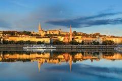 布达佩斯市的Buda边前面看法反射在多瑙河中寂静的水的  图库摄影