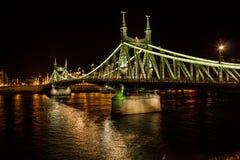 布达佩斯都市风景在晚上 在前面的铁锁式桥梁在多瑙河 免版税库存照片