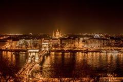 布达佩斯都市风景在晚上 在前面的铁锁式桥梁在多瑙河 免版税库存图片