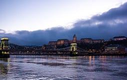 布达佩斯都市风景在晚上 在前面的铁锁式桥梁在有城堡的多瑙河在背景中 免版税库存图片