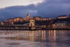 布达佩斯都市风景在晚上 在前面的铁锁式桥梁在有城堡的多瑙河在背景中 库存照片
