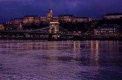 布达佩斯都市风景在晚上 在前面的铁锁式桥梁在有城堡的多瑙河在背景中 图库摄影