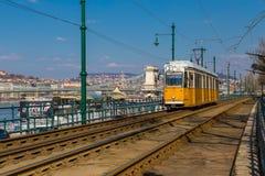 布达佩斯,匈牙利, 2018年3月22日:黄色电车在与多云天空的早期的冬天 电车第2为是著名的 图库摄影