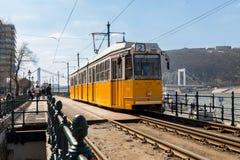 布达佩斯,匈牙利, 2018年3月22日:黄色电车在与多云天空的早期的冬天 电车第2为是著名的 免版税库存照片