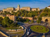 布达佩斯,匈牙利-克拉克亚当广场环形交通枢纽从上面在与布达城堡王宫的日出 免版税库存照片