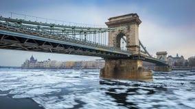 布达佩斯,匈牙利-在冰冷的河多瑙河的著名Szechenyi铁锁式桥梁在一个冷的冬天早晨 库存图片