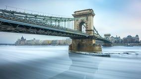 布达佩斯,匈牙利-在冰冷的河多瑙河的著名Szechenyi铁锁式桥梁在一个冷的冬天 免版税库存照片