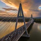 布达佩斯,匈牙利-在河多瑙河与繁忙运输的日落的,美丽的剧烈的云彩的Megyeri桥梁 库存照片