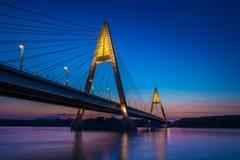布达佩斯,匈牙利-在河多瑙河的有启发性Megyeri桥梁在蓝色小时 免版税库存照片