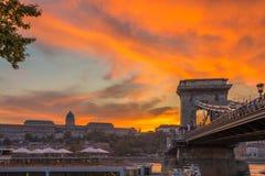 布达佩斯,匈牙利-在Szechenyi铁锁式桥梁的美好的剧烈的金黄日落有布达城堡王宫的 免版税图库摄影