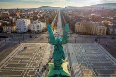 布达佩斯,匈牙利-天使雕塑从后面在英雄在日落的`正方形上面  库存图片