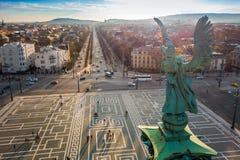 布达佩斯,匈牙利-天使雕塑从后面在英雄在日落的`正方形上面  图库摄影
