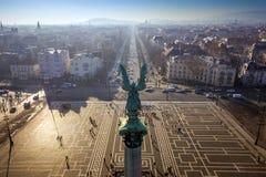 布达佩斯,匈牙利-天使雕塑从后面在英雄`正方形上面  免版税图库摄影