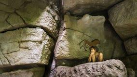 布达佩斯,匈牙利- 2018年6月01日:坐在洞艺术之间的一个年轻穴居人男孩的模型绘了岩石 库存图片