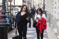 布达佩斯,匈牙利- 2018年4月9日:步行沿着向下街道的两个俏丽的女孩 库存照片