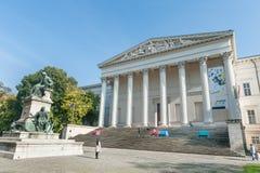 布达佩斯,匈牙利- 2015年10月26日:有当地人民的布达佩斯宫殿坐五颜六色长凳和读 背景madonna老宗教信仰雕象 免版税库存图片