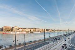 布达佩斯,匈牙利- 2015年10月27日:桥梁和多瑙河的风景在布达佩斯,匈牙利 人们等待电车 图库摄影