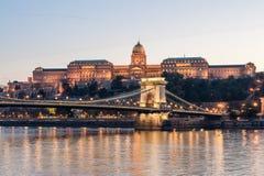 布达佩斯,匈牙利- 2015年10月30日:铁锁式桥梁、多瑙河和王宫在布达佩斯,匈牙利 晚上照片写真 图库摄影