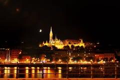 布达佩斯,匈牙利-河多瑙河,圣马赛厄斯和渔夫` s教会本营在晚上 免版税库存照片