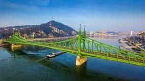 布达佩斯,匈牙利-美丽的自由桥梁Szabadsag空中全景掩藏了与去在河多瑙河的驳船 免版税库存图片