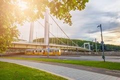 布达佩斯,匈牙利-通过在Elisabeth桥梁下的传统黄色电车在多瑙河 库存照片
