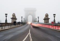 布达佩斯,匈牙利- 26, 12月 铁锁式桥梁在布达佩斯,匈牙利,雾的 红绿灯和未知的人民 免版税库存照片