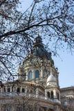 布达佩斯,匈牙利- 02/19/2018 :圣斯蒂芬有露出的树前景的` s大教堂反对清楚的蓝天 宗教结构 免版税库存照片