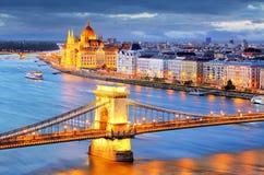 布达佩斯,铁锁式桥梁夜视图在多瑙河的 图库摄影