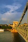 布达佩斯 匈牙利- 2016年7月26日:晚上在雨以后的布达佩斯,对铁锁式桥梁的一个看法和彩虹的一个金黄小时 免版税图库摄影
